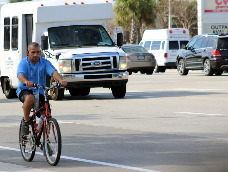 Man riding a bicycle in crosswalk in West Palm Beach, FL